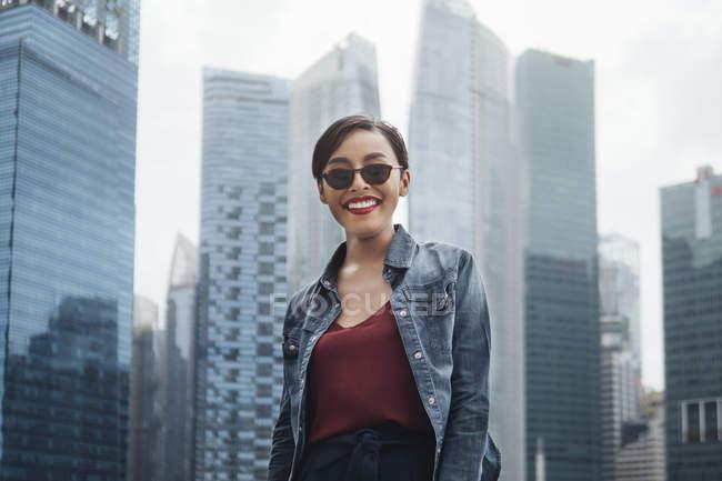 Joven dama singapurense sonriendo a la cámara y posando con rascacielos en Singapur . - foto de stock