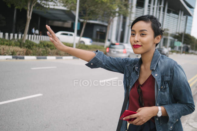 Young Malay Singaporean lady having a portrait session with repeated horizontal lines as background. — Stock Photo