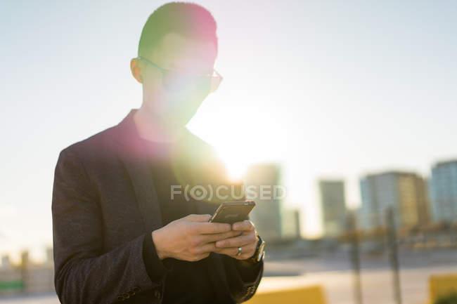 Jovem asiático homem em óculos de sol usando smartphone — Fotografia de Stock