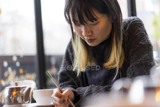 Jovem atraente casual mulher asiática escrever notas no café — Fotografia de Stock