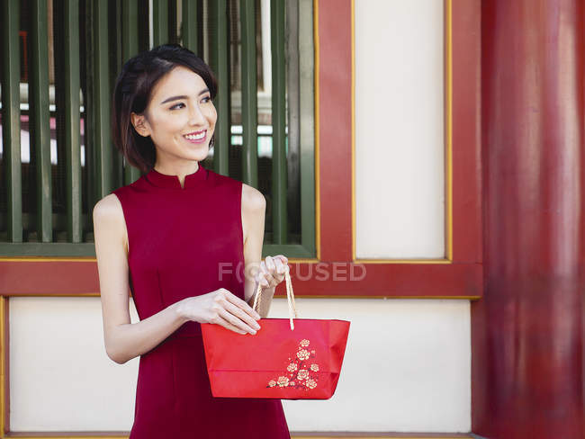 Chinese woman with red purse smilng outdoors — Stock Photo
