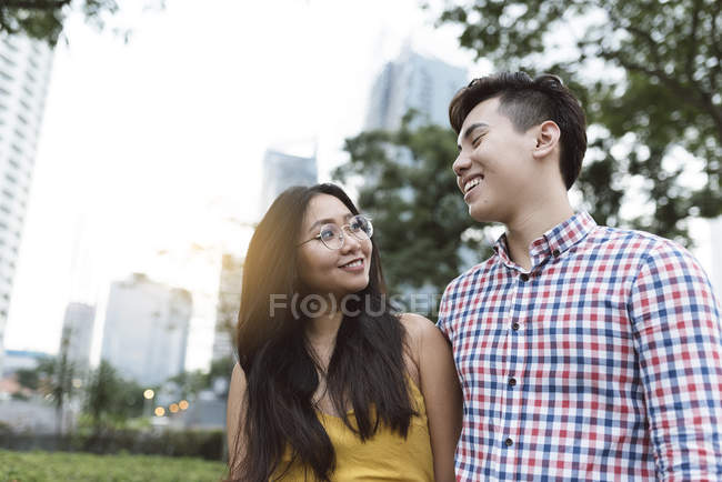 Young asian couple walking together in city — Stock Photo
