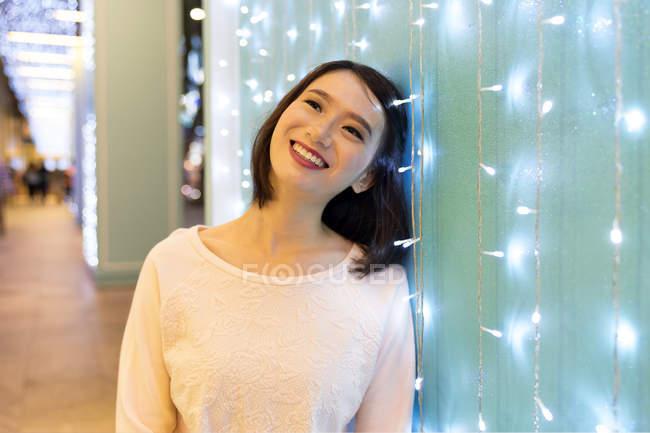 Joven atractivo asiático mujer retrato cerca guirnalda - foto de stock