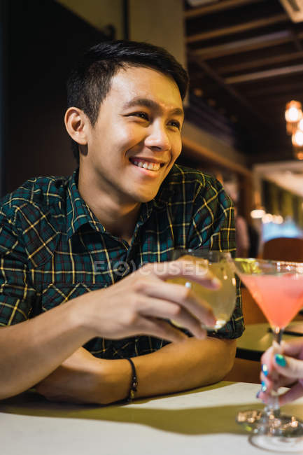 Young asian man with cocktail in comfortable bar — Stock Photo