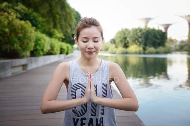 Jeune sportive asiatique femme faire yoga à jetée — Photo de stock