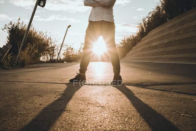 Обрезанное изображение молодых азиатских человека, стоящего на фоне заката со скрещенными руками — стоковое фото