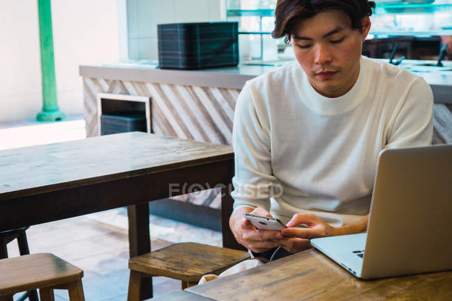 Asian man using digital devices in cafe — Stock Photo