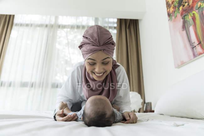 Азиатская мусульманская мать и ребенок играют на кровати — стоковое фото