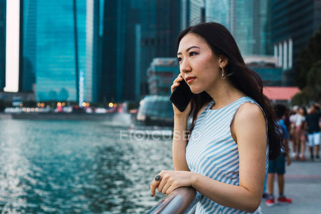 Jeune asiatique femme en utilisant smartphone contre gratte-ciel — Photo de stock