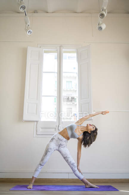 Young asian woman doing stretching exercises against window — Stock Photo