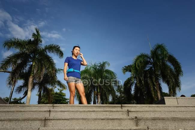 Giovane donna asiatica sportiva in piedi vicino a passi — Foto stock