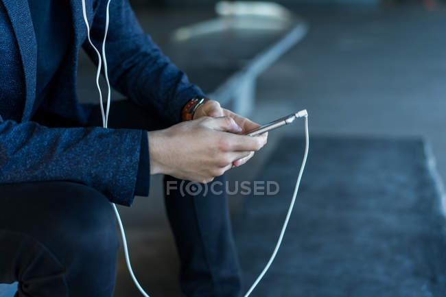 Обрезанный образ человека с помощью смартфона, вид сбоку — стоковое фото
