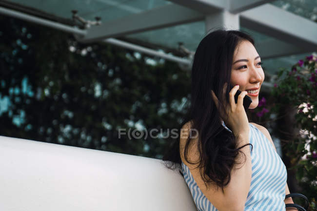 Young asian woman speaking on smartphone outdoors — Stock Photo