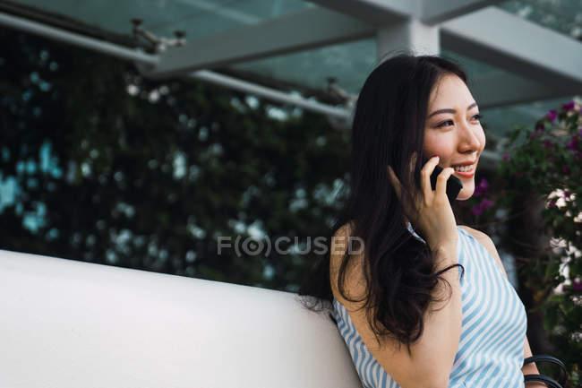 Mujer asiática joven hablando en el teléfono inteligente al aire libre - foto de stock