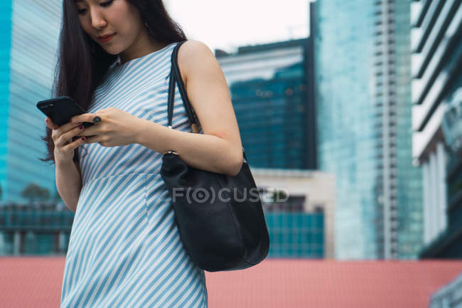 Young asian woman using smartphone on street — Stock Photo
