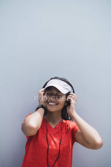 Young asian sporty woman using headphones against grey wall — Stock Photo