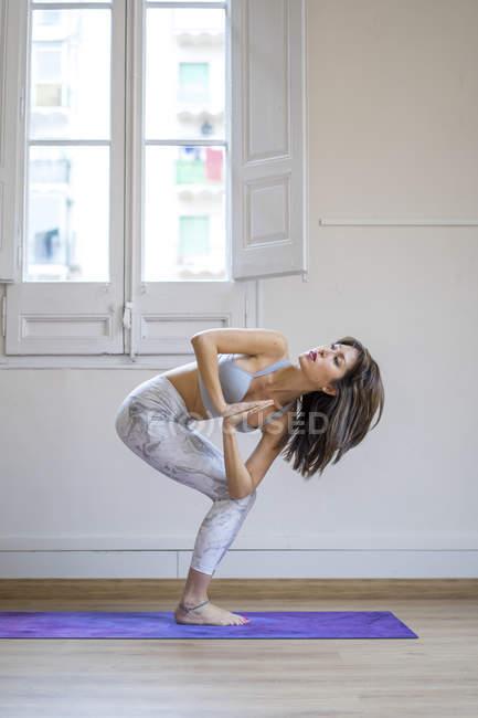 Young asian woman doing yoga exercise on mat, prayer twist pose — Stock Photo
