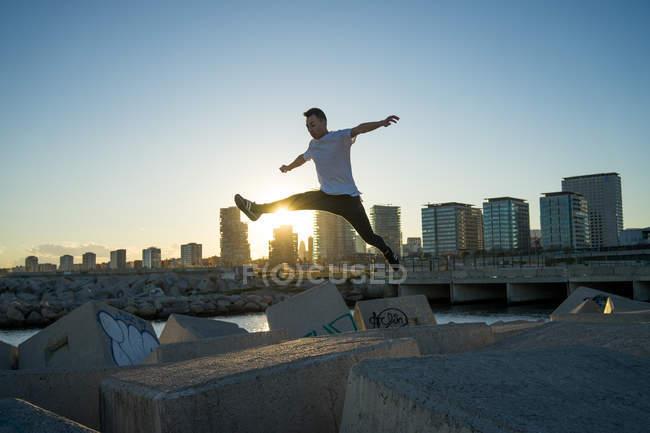 Jovem asiático homem jumping no blocos no por do sol — Fotografia de Stock