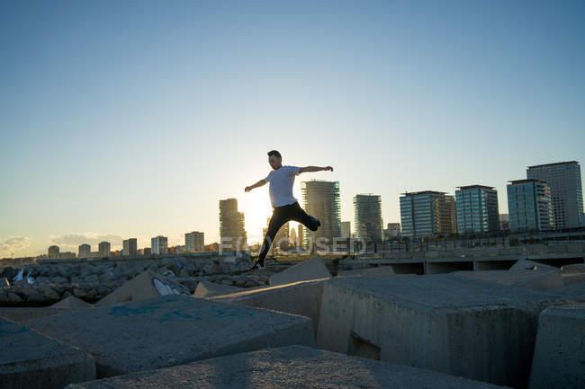Young asian man jumping on blocks at sunset — Stock Photo
