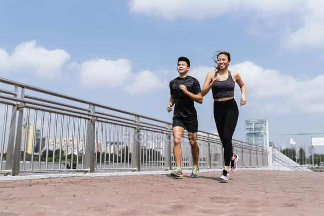 Счастливая азиатская спортивная пара бегает в городе вместе — стоковое фото