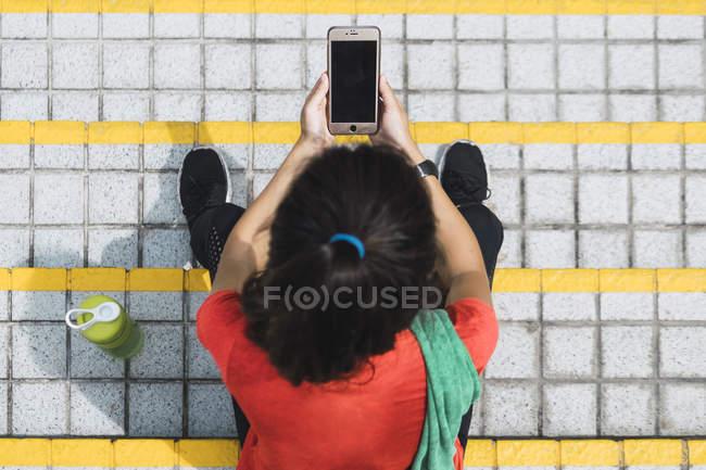 Joven asiático deportivo mujer usando smartphone en escaleras, vista elevada - foto de stock