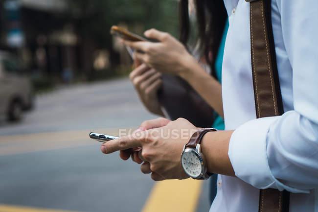Обрезанный образ взрослой деловой пары с помощью смартфонов — стоковое фото