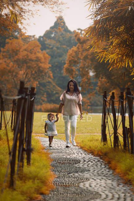 Bonito asiático mãe e filha andando no caminho no parque — Fotografia de Stock