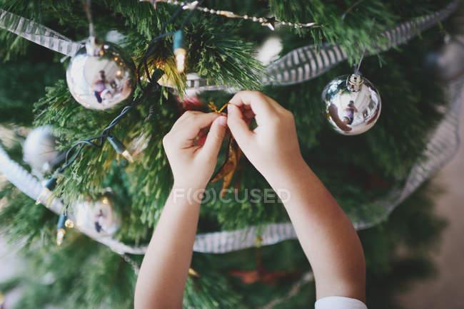 Famiglia asiatica che celebra le vacanze di Natale, immagine ritagliata del ragazzo che decora l'abete — Foto stock