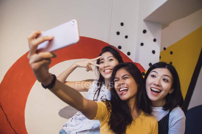 Jóvenes asiático mujeres tomando selfie en creativo moderno oficina - foto de stock