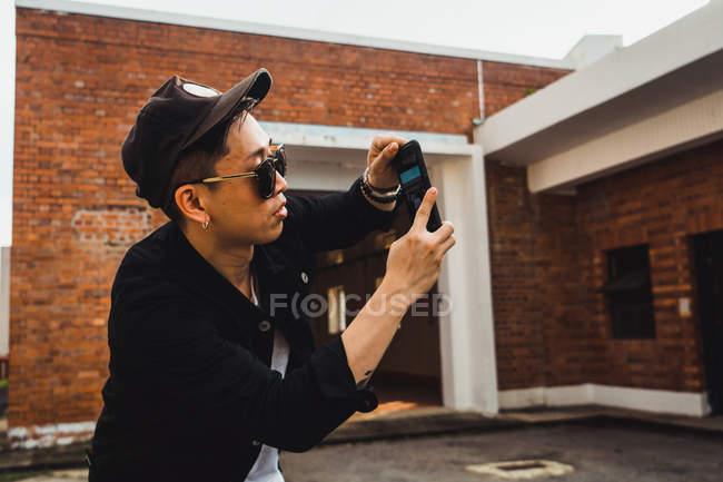 Legal jovem asiática usando smartphone ao ar livre — Fotografia de Stock