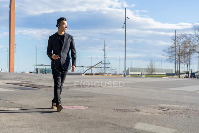 Jovem asiático homem com fone de ouvido andando na cidade — Fotografia de Stock