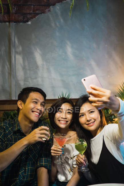 Young asian friends taking selfie in comfortable bar — Stock Photo