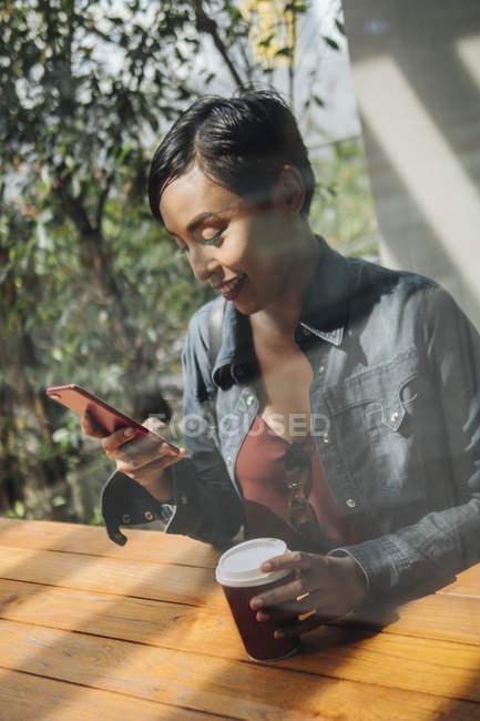 Ritratti di giovane signora di Singaporean malese godendo se stessa con il suo telefono di fuori — Foto stock