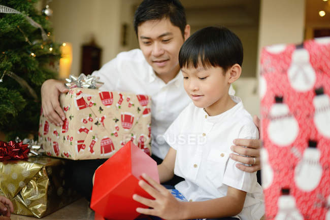 Happy asian family at christmas holidays, father and son holding presents — christmas tree, christian holiday - Stock Photo | #212707874