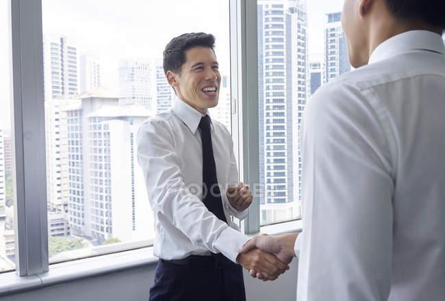Красивий азіатських бізнесменів вітають один одного в офісі — стокове фото