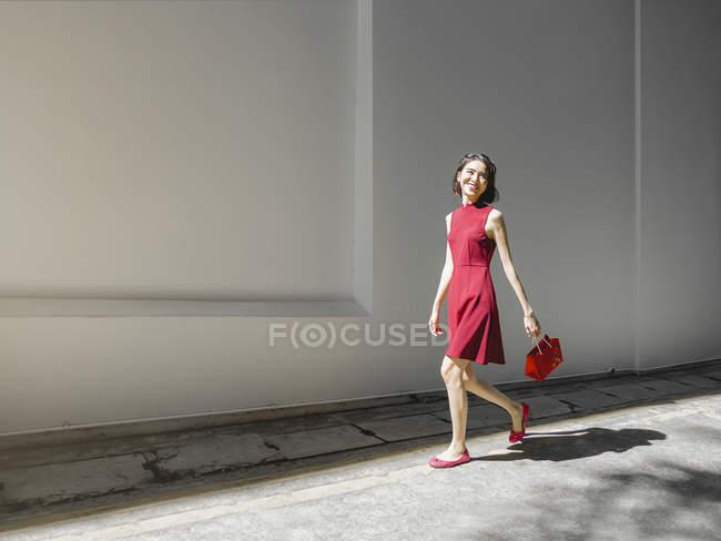 Китайська Жінка вигулює білі стіни з гаманець — стокове фото