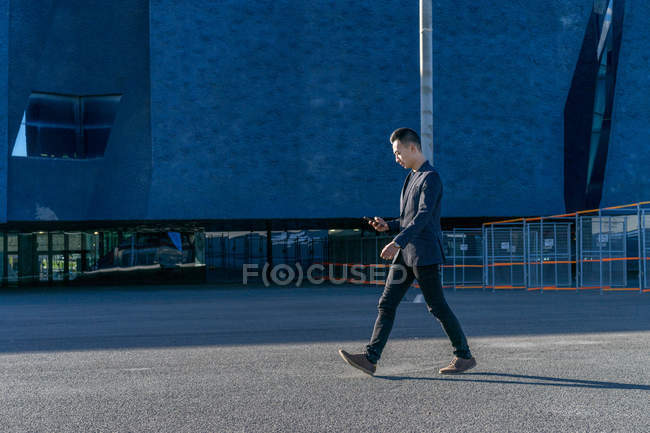 Молодой азиат ходит по улице со смартфоном — стоковое фото