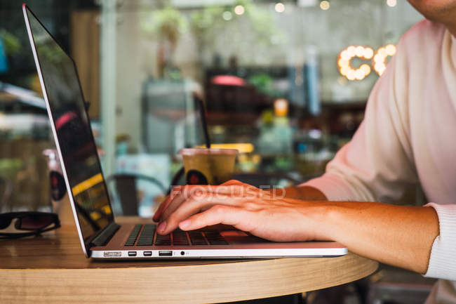 Cropped image of man using laptop on table — Stock Photo
