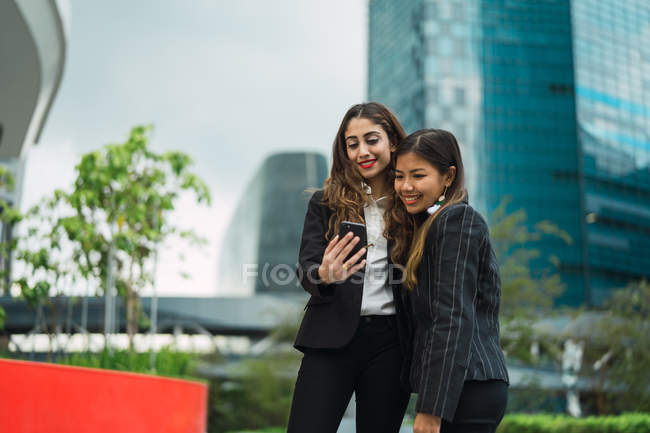 Young asian business women using smartphone — Stock Photo