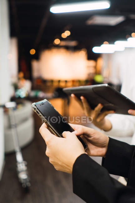 Cropped image of business people using digital devices in modern office — Stock Photo