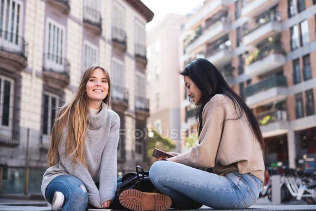 Dois amigos olhando para seu smartphone nas ruas de Madrid — Fotografia de Stock