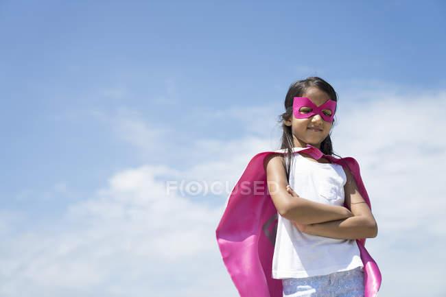 Little cute girl dressed like superhero under blue sky — Stock Photo