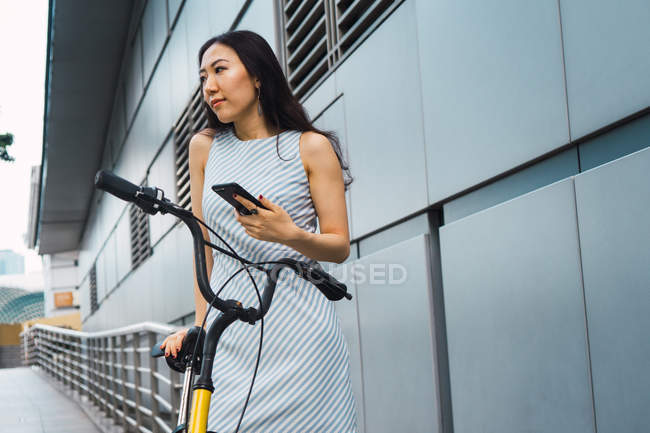 Young asian woman with smartphone and bike — Stock Photo