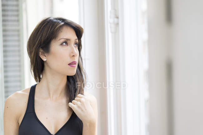 Young asian woman  standing near window — Stock Photo