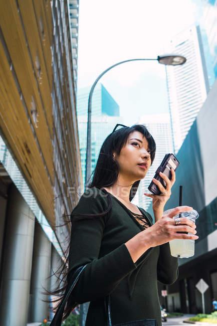 Junge Asiatin benutzt Smartphone und trinkt — Stockfoto