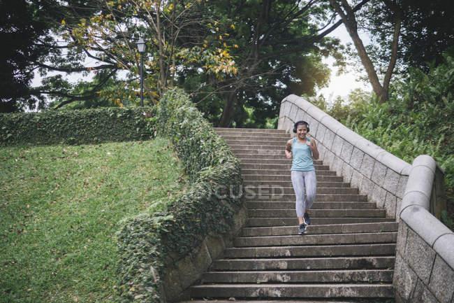 Giovane asiatica donna sportiva che corre sulle scale nel parco — Foto stock