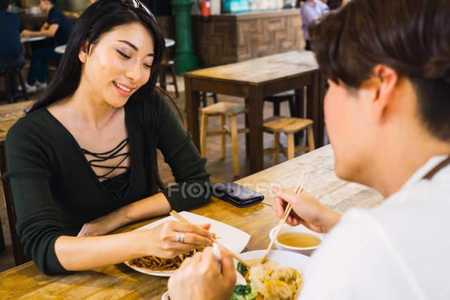 Junge asiatische Paar Essen im café — Stockfoto