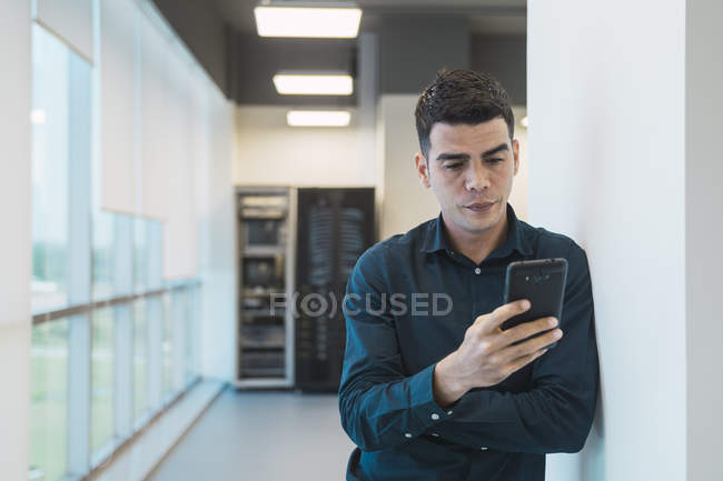 Homme d'affaires asiatiques jeunes utilisant smartphone dans le bureau moderne — Photo de stock