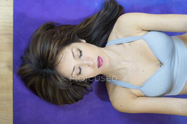 Young asian woman lying on mat with closed eyes — Stock Photo