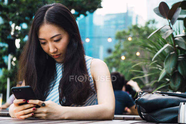 Portrait of young asian woman using smartphone — Stock Photo